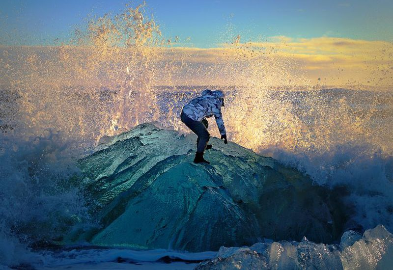 The tourist got onto the iceberg to have his photo taken.