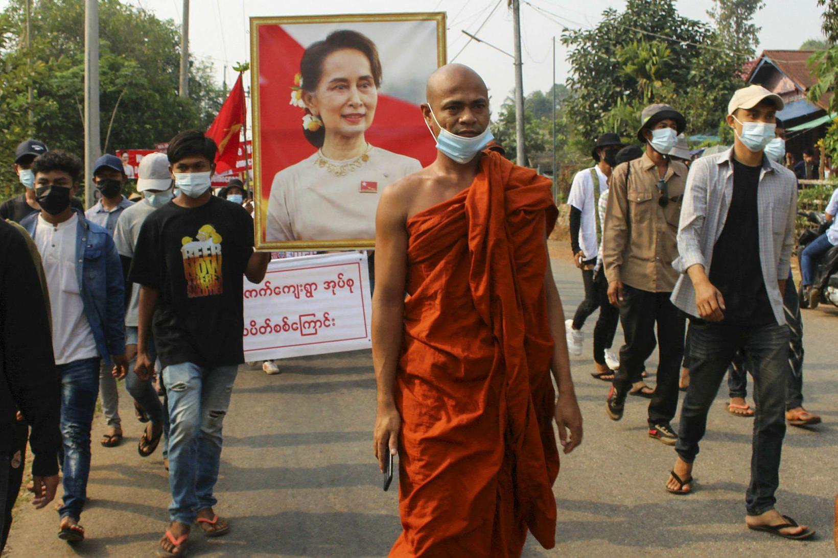 Mótmælendur ganga um götur Mjanmar.
