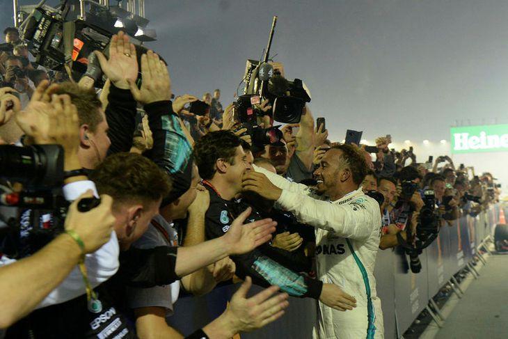 Lewis Hamilton fagnar með liðsfélögum sínum í Singapúr í dag.