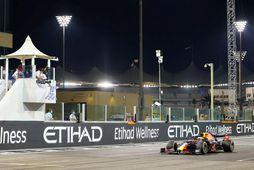 Sigurfánanum veifað til Max Verstappen er hann rennnir sér yfir endamarkið í Abu Dhabi.