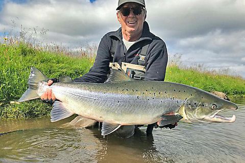 Eric Clapton with his giant salmon on Friday.  .