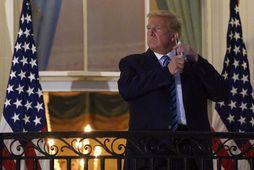 Donald Trump forseti Bandaríkjanna sést hér taka af sér grímuna þegar hann er kominn heim …