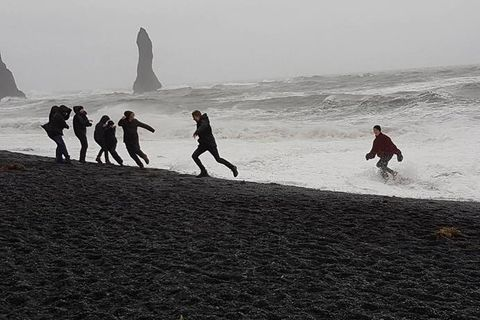 Tourists running into the waves and laughing at Iceland's most dangerous beach.