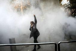 Mótmælandi í reykjarmekki við háskólann í Teheran eftir að öryggissveitir beittu áragasi.