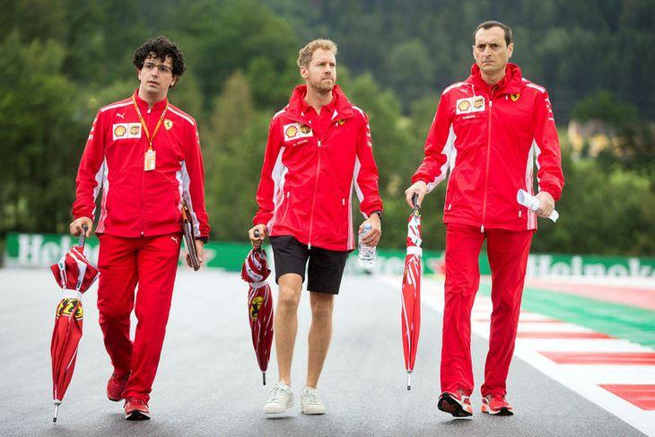 Sebastian Vettel (fyrir miðju) skoðar brautina í Speilberg í Austurríki ásamt nokkrum vélfræðingum sínum. Regnhlífar ...