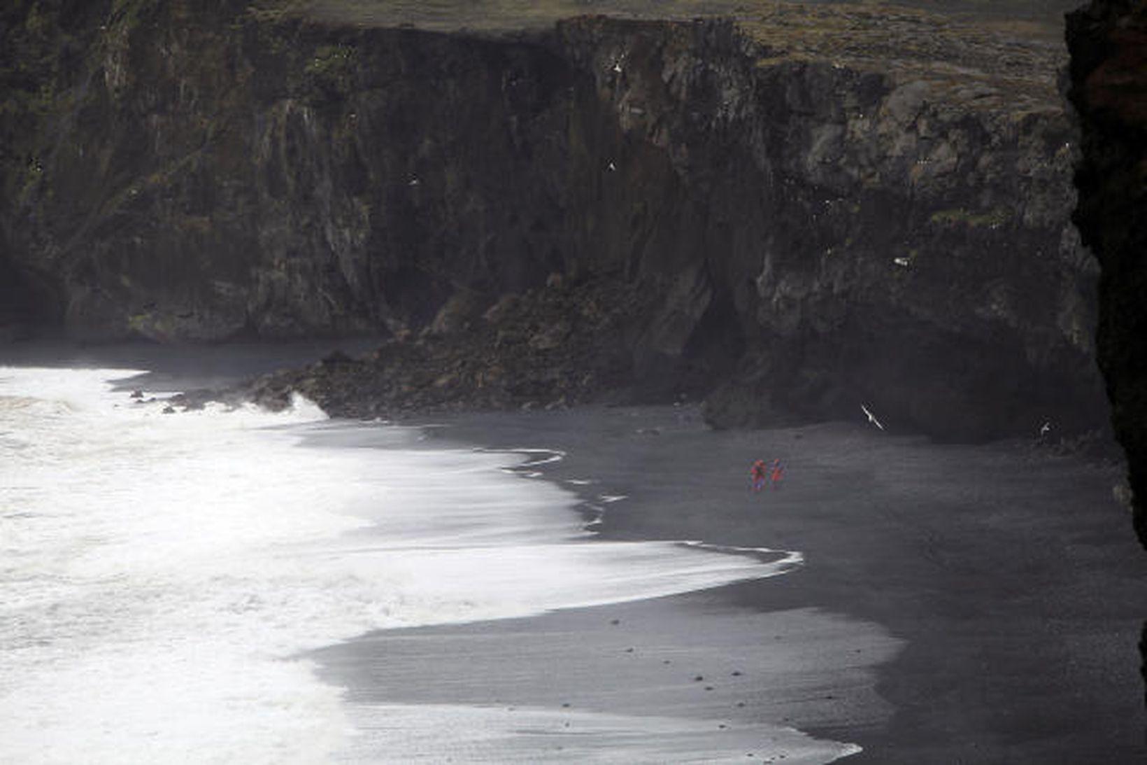 Björgunarsveitarmennirnir eru smáir undir hömrunum við Kirkjufjöru þar sem fólkið …