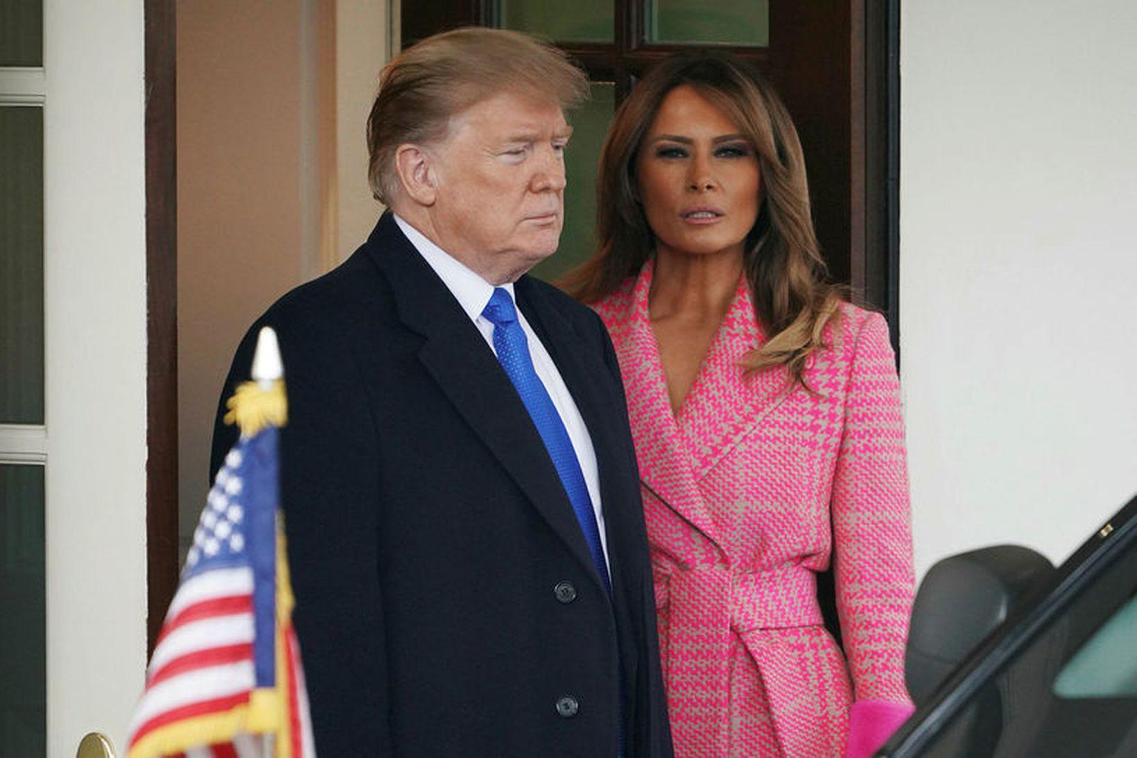 Melania Trump í bleiku kápunni ásamt eiginmanni sínum Donald Trump.