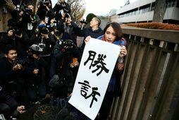 Japanska blaðakonan Shiori Ito með sigurspjaldið fyrir utan réttarsalinn í dag.