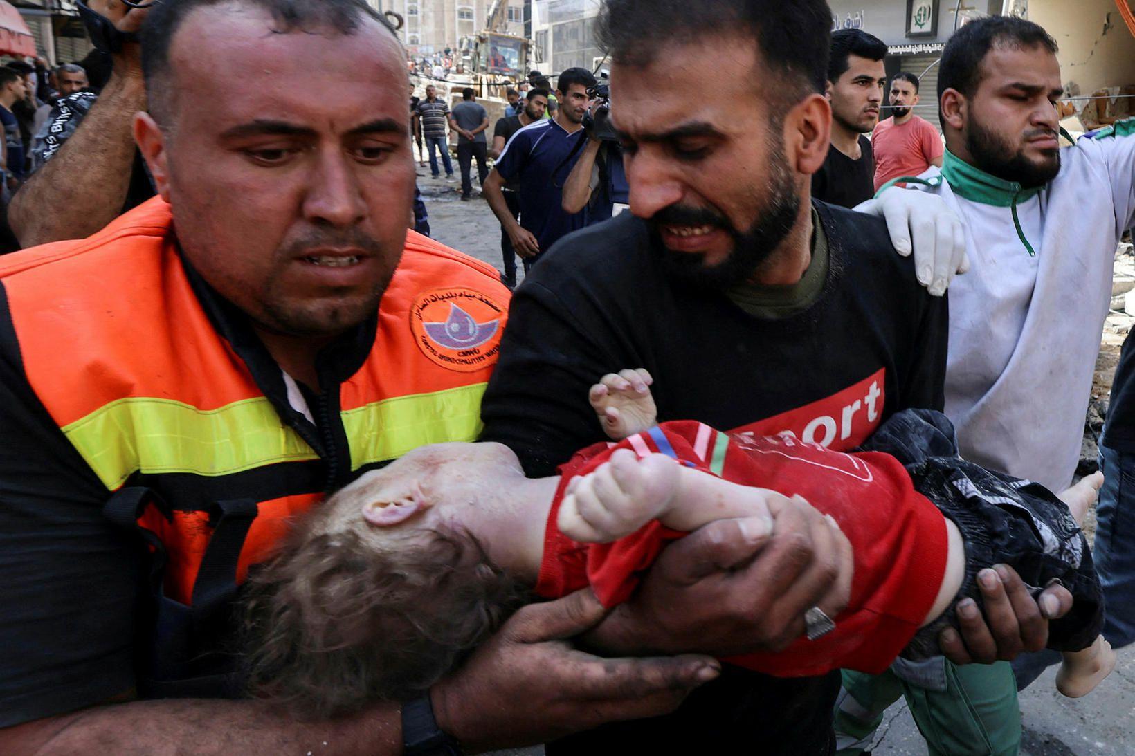 Palestínskar björgunarsveitir með lík barns sem varð undir heimili sínu …