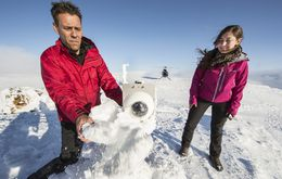 Bjarni Björnsson and Hanna Reynolds wipe snow off the lens of a webcam pointed at …