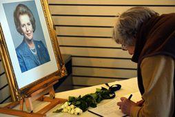 Kona ritar nafn sitt í minningarbók um Thatcher í Grantham safninu á Englandi í dag.
