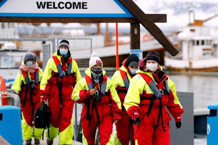 Tourists in the town of Husavik return from whale watching, thoroughly masked and protected from …