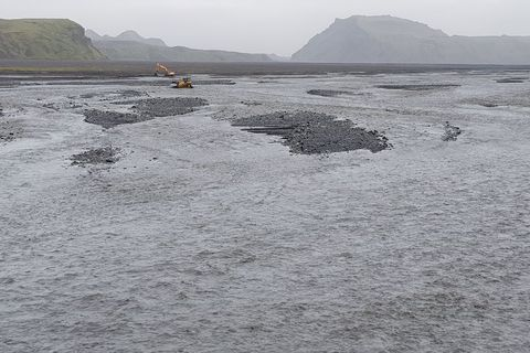 A bulldozer creating channels in the river to prevent the road and bridge from being destroyed.