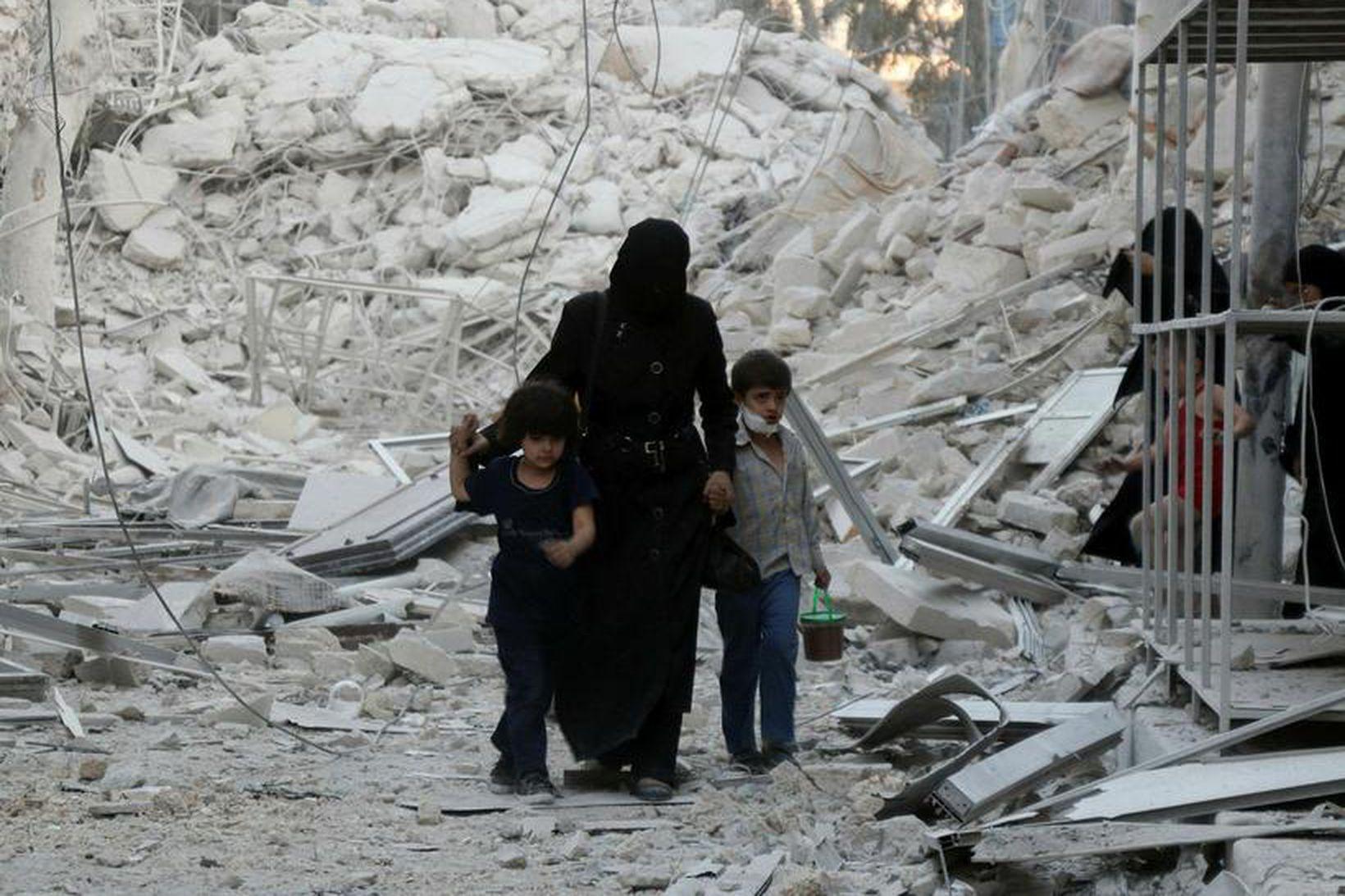 Sýrlensk fjölskylda virðir fyrir sér eyðilegginguna í Aleppo þar sem …