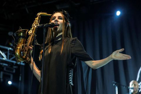 PJ Harvey dressed in black and wearing feathers on her head brandishing a saxofone at the Vodafone hall in Reykjavik last night.