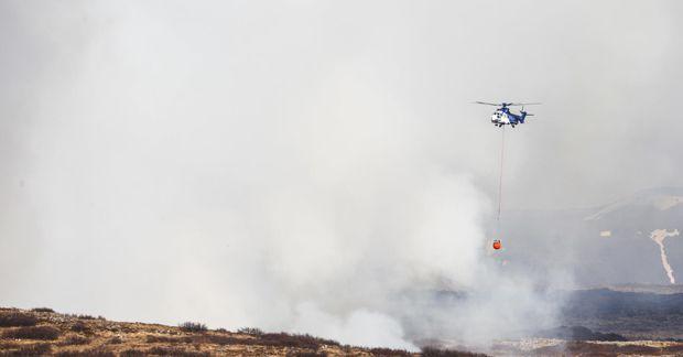 TF-EIR á flugi yfir Heiðmörk með slökkviskjóluna sem ónýttist við starfið.