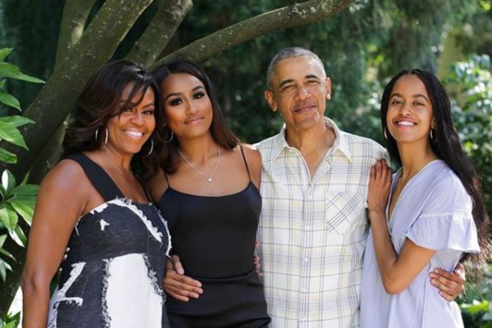 Sasha Obama stendur á milli foreldra sinna.