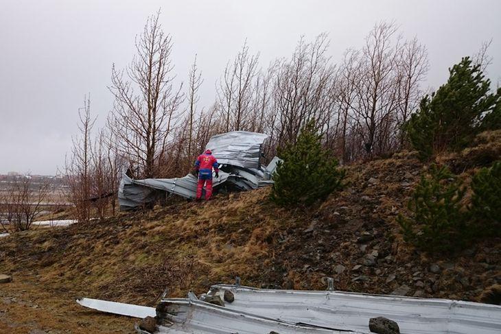 Björgunarsveitarmaður við þakplöturnar sem fuku í Víðidal.