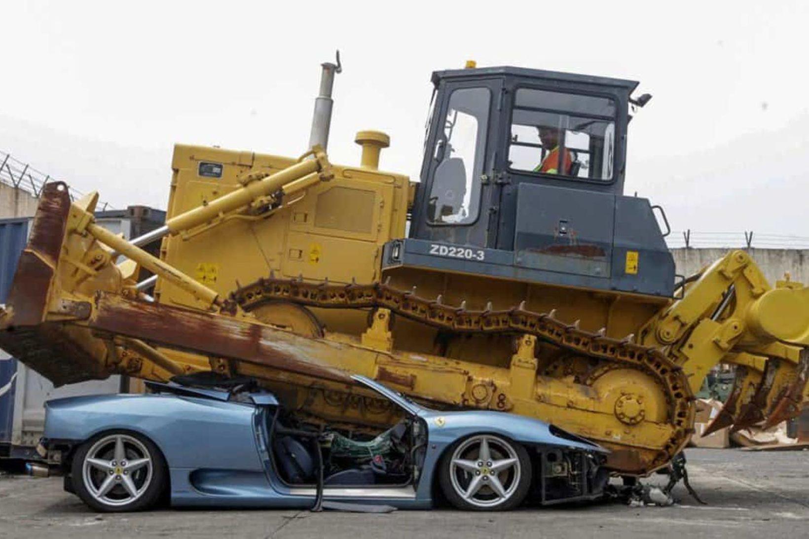 Ferrari 360 Spider ofursportbíllinn leggst saman undan farginu sem jarðýtan …