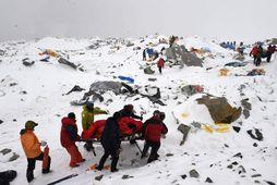 Slasaður fjallgöngumaður fluttur á börum í grunnbúðum Everest eftir snjóflóðin í apríl.