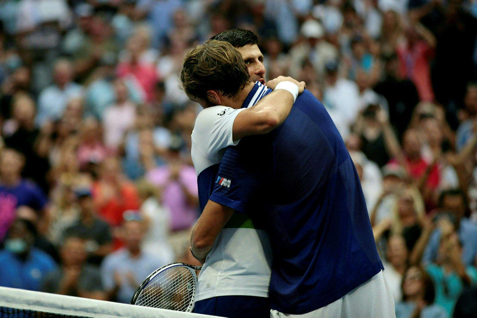 Novak Djokovic og Daniil Medvedev fallast í faðma eftir viðureignina …