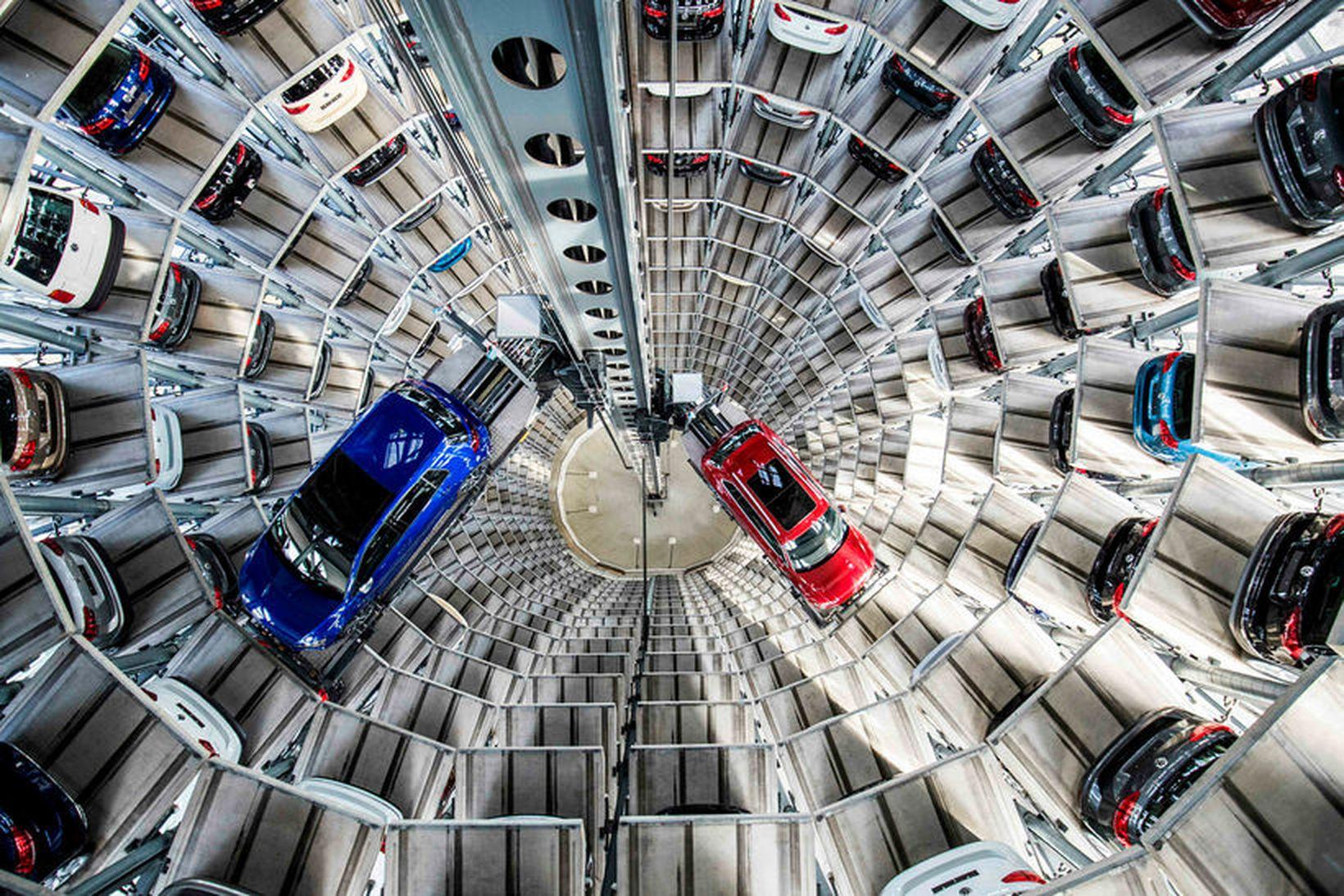 Bílum staflað í hillur í bílageymslu Volkswagen í Wolfsburg. Hópmál …