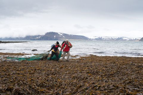 Two of the group removing an old net from the beach.