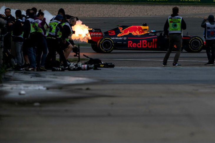 Eldur stígur upp af bíl Daniel Ricciardo á lokaæfingunni í Sjanghæ í morgun.
