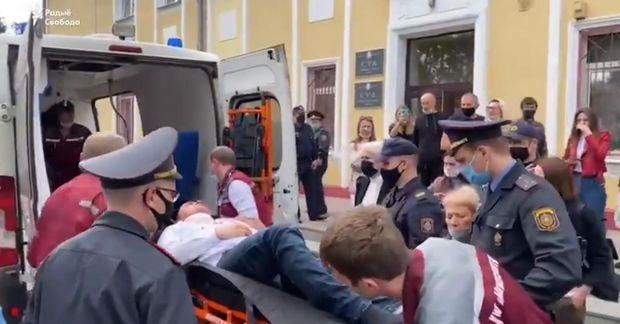 Lögreglumenn og bráðaliðar bera Latypau upp í sjúkrabíl fyrir utan dómshús í Minsk.