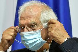 Josep Borrell lagar grímuna sína.