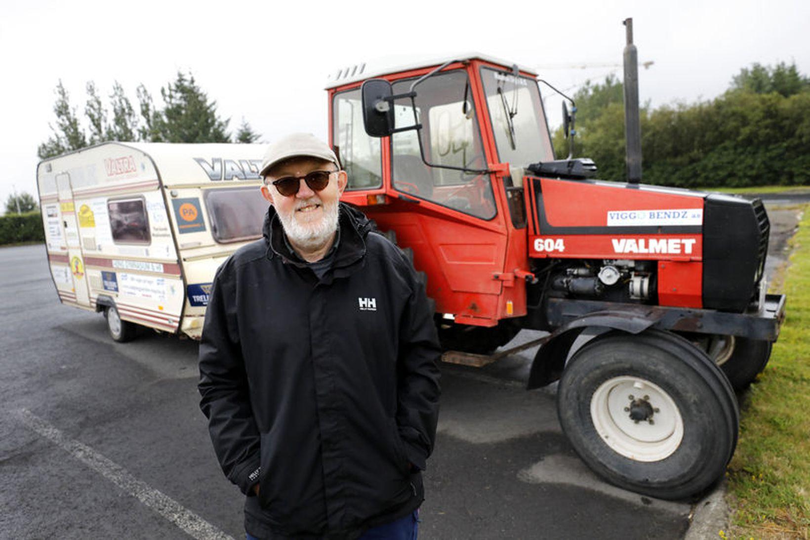 Kurt fyrir framan traktorinn sinn og húsvagn.