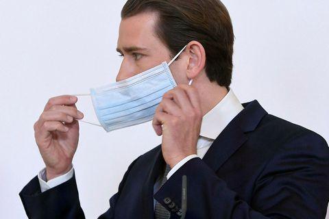 Sebastian Kurz tekur af sér andlitsgrímu á blaðamannafundi.