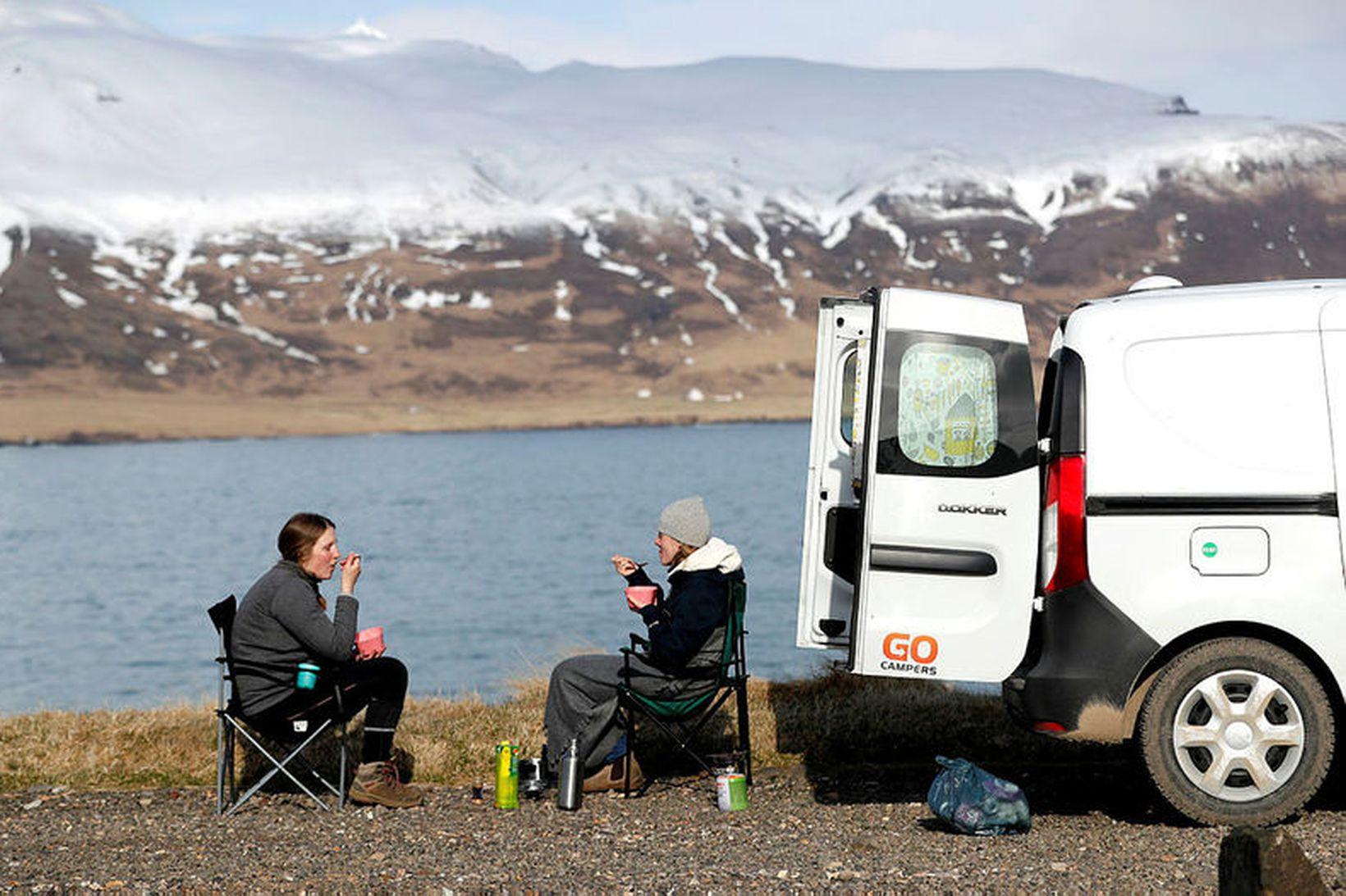 Ferðamenn njóta sín við Hafnarhólma í Borgarfirði eystra. Bílaleigubílum í …