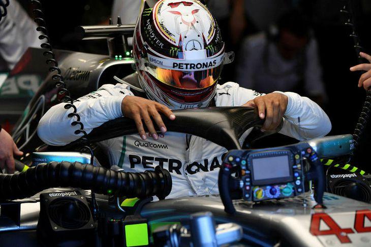 Lewis Hamilton smokrar sér niður í stjórnklefa Mercedesbílsins við upphaf æfingarinnar í Melbourne.