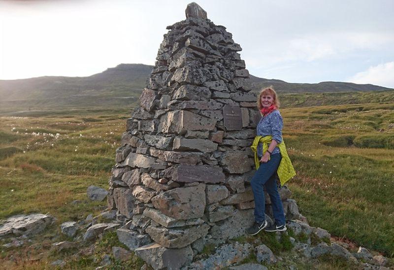Kristín Steinsdóttir next to the memorial for Dísa, the famous ghost of Seyðisfjörður.