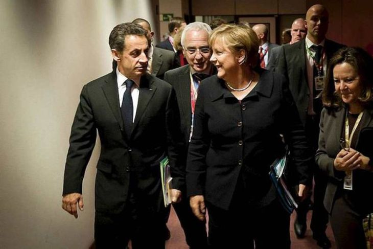Germany's Chancellor Angela Merkel and France's President Nicolas Sarkozy (L) talk while on their way ...