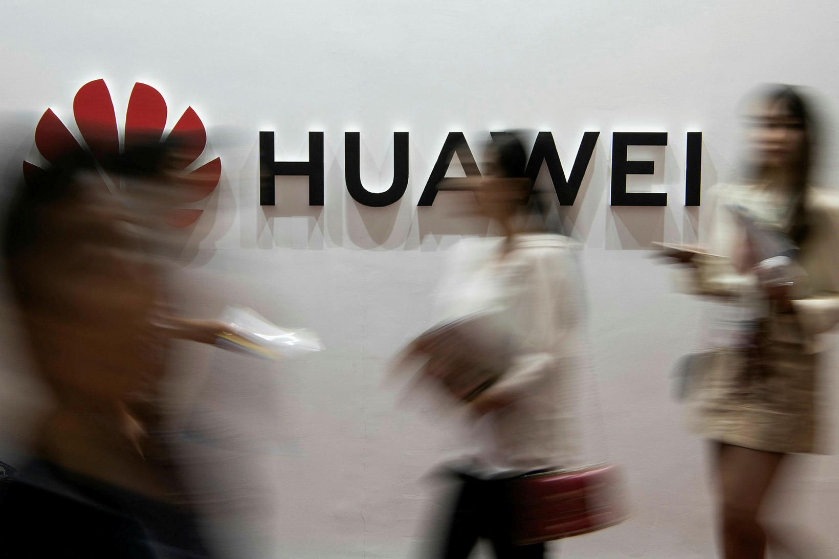 Fólk gengur fram hjá lógói Huawei í Peking í fyrra.