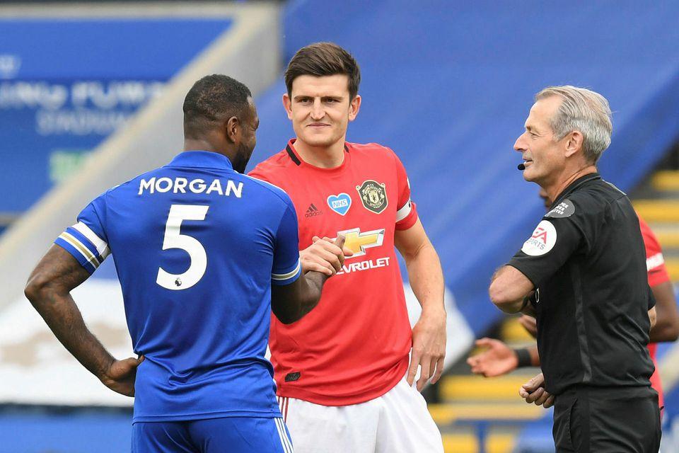 Harry Kane og Wes Morgan takast í hendur í leik Leicester og Manchester United.