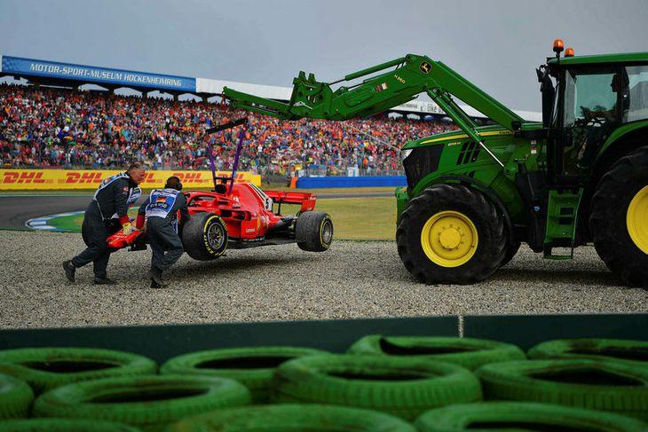 Dráttarvél flytur Ferrarifák Sebastian Vettel af vettvangi í Hockenheim.