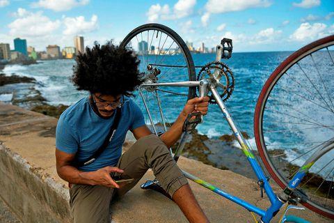 Íbúi Havana staldrar við strandgöngugötuna vinsælu í borginni.