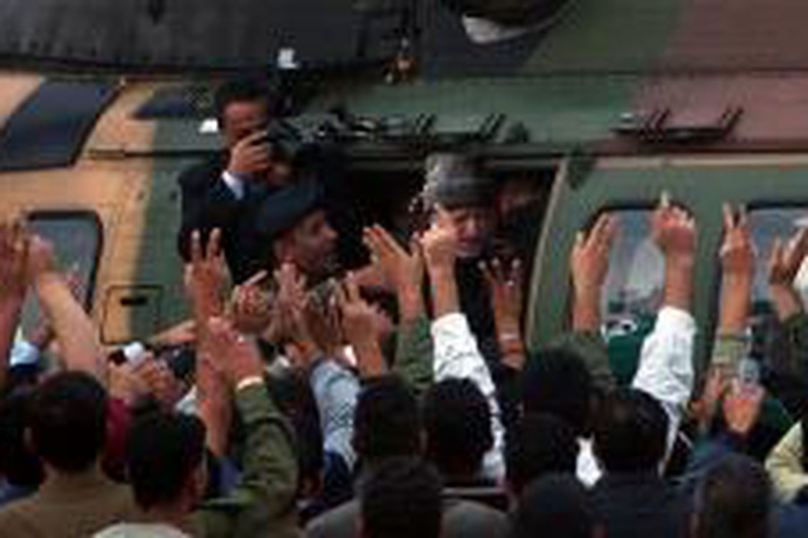 Hópur manna veifar til Arafats þegar hann fer um borð …