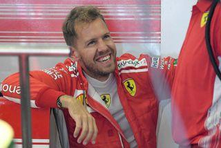 Sebastian Vettel slær á létta strengi við vélvirkja í bílskúr Ferrari milli aksturslota á þriðju ...