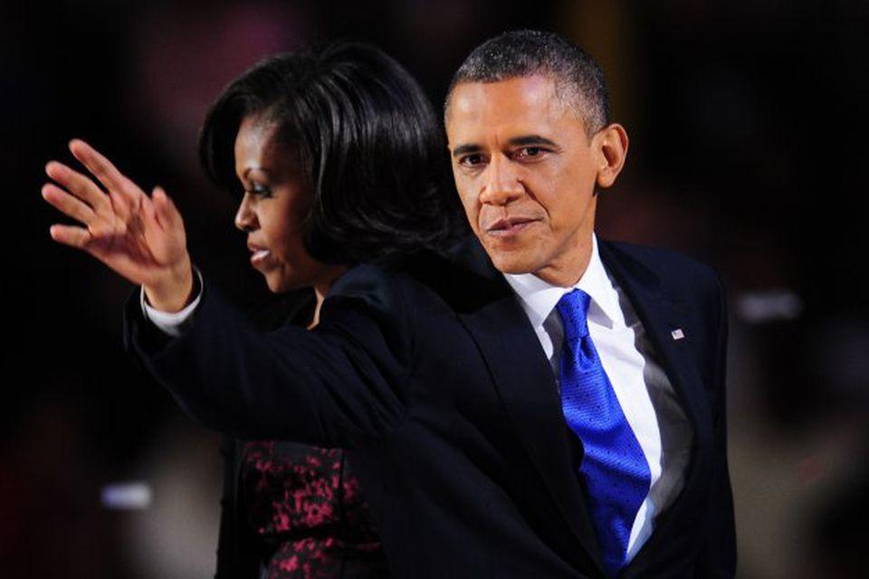 Barack Obama veifar til stuðningsmanna sinna. Eiginkonan Michelle við hlið hans á sviðinu.