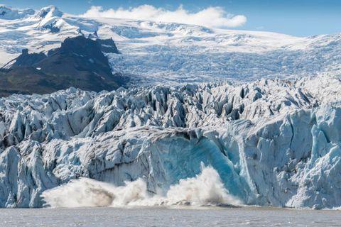 A large chunk of ice from Fjallsjökull glacier falls into Fjallsárlón glacial lagoon.