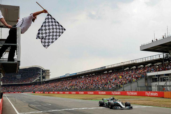Lewis Hamilton á Mercedes ekur fyrstur yfir marklínuna í Hockenheim.