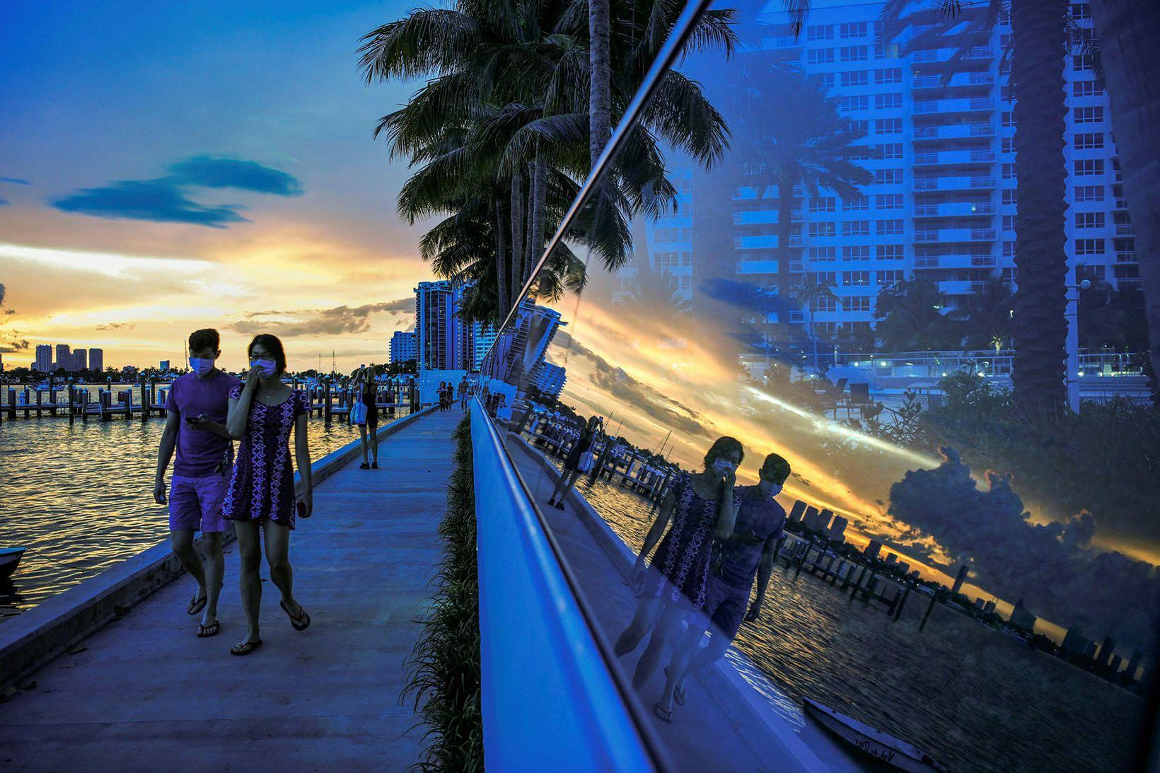 Fólk á gangi við sólsetur á Miami-strönd í sumar. Kjósendur …