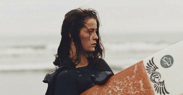 Halla Líf Hjálmarsdóttir fer í kaldan íslenskan sjóinn á brimbretti. Hér er hún með brettið …