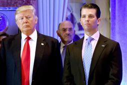 Donald Trump, fyrrverandi Bandaríkjaforseti, ásamt syni sínum Donald, Jr. Í bakgrunni má sjá glitta í …