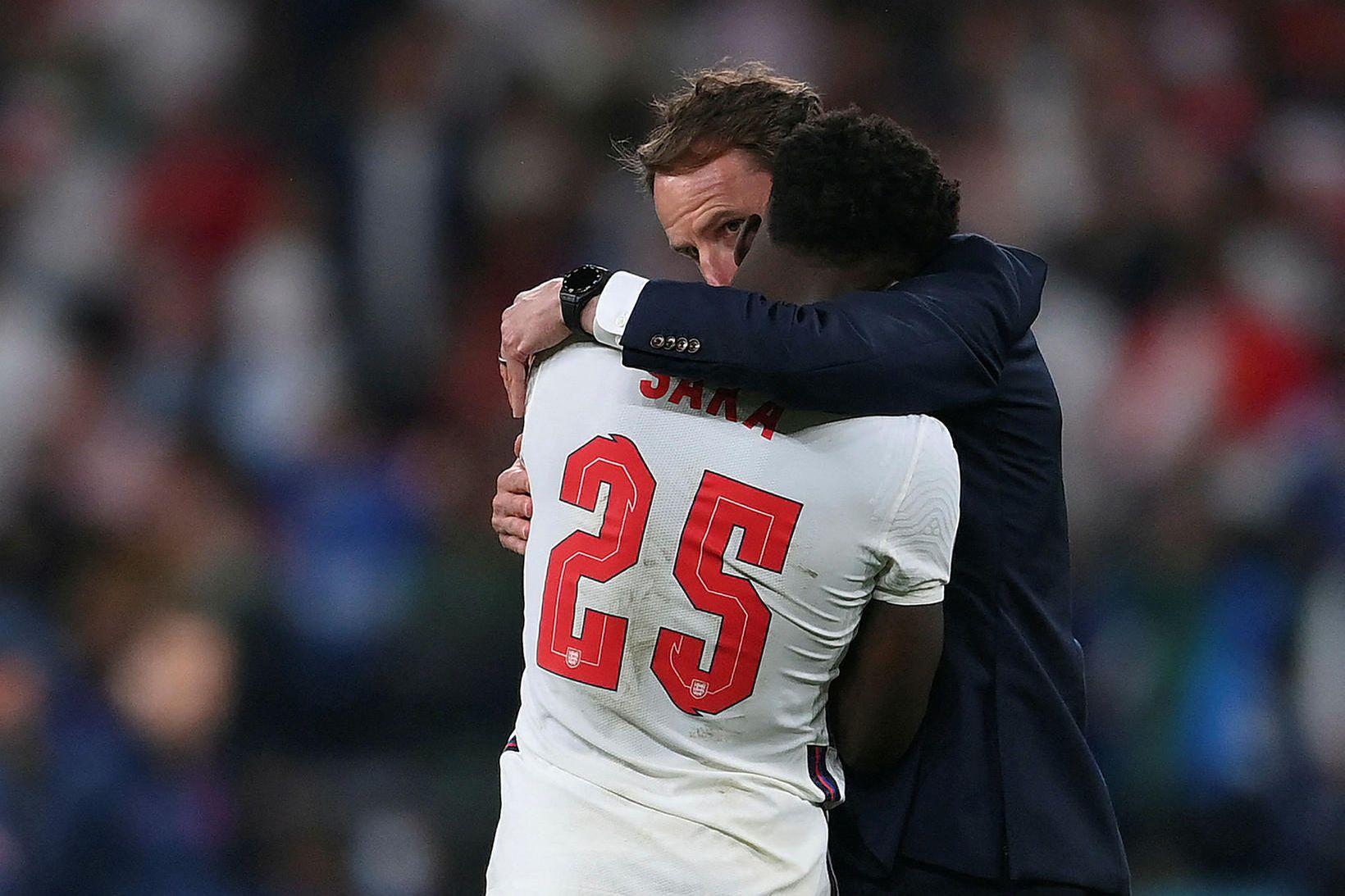 Gareth Southgate huggar Bukayo Saka á Wembley um liðna helgi.