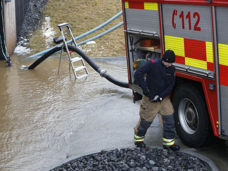 The fire department clearing out water from a flooded car parking cellar.